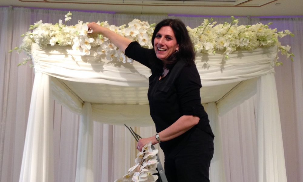 Image of Jeri Solomon decorating Huppah for Wedding with Flowers